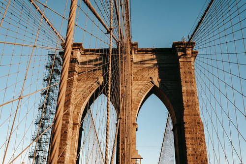 From below of suspension Brooklyn bridge with brick arch and ropes against blue sky in New York