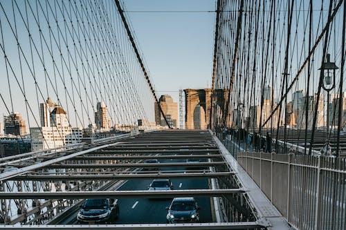 Metal suspension bridge with traffic in city