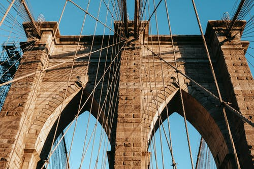Low angle of famous Brooklyn brick arches with ropes on top of bridge in metropolis