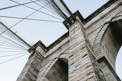 From below of brick elements on structure with cables on Brooklyn bridge against clear sky