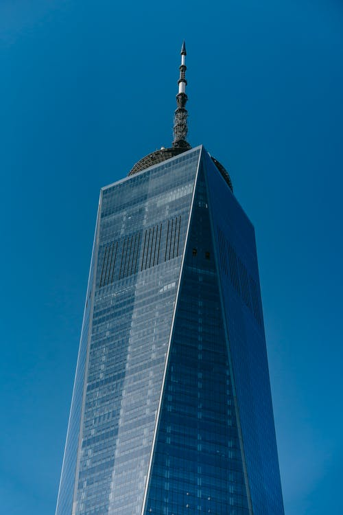 From below of glass facade of high rise building with tower on roof against clear blue sky