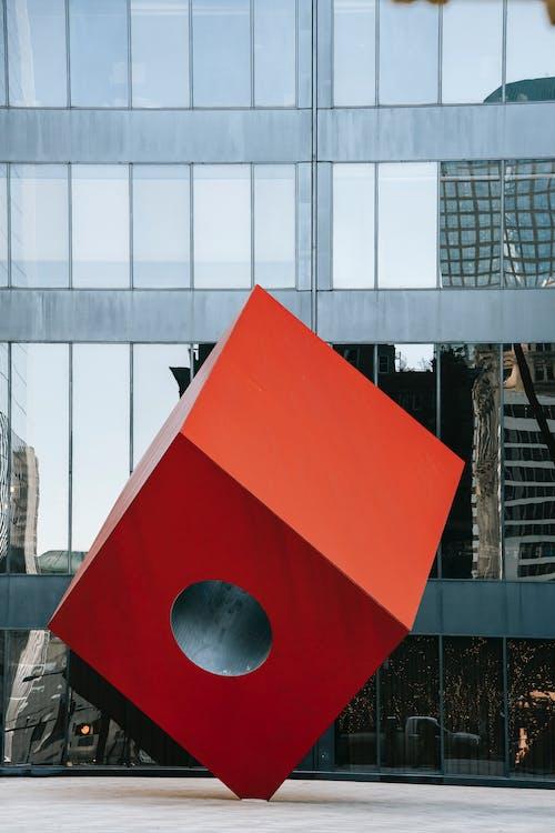 現代の街の広場にある未来的な赤い立方体の彫刻