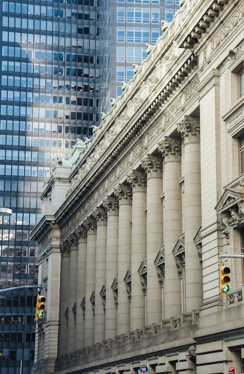 Majestic stone building near glass skyscraper in downtown