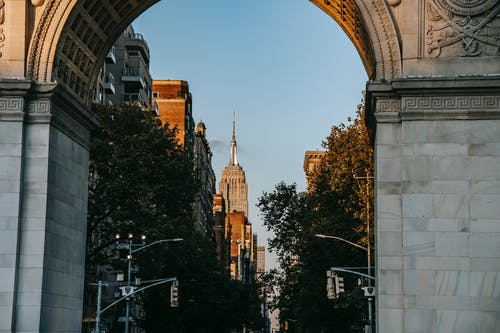 View through ancient arch on street leading to famous skyscraper in New York City in sunny day