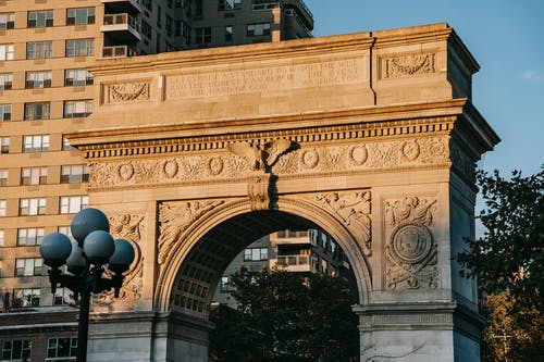 From below of aged triumphal arch placed in Washington Square Park in New York City against residential building illuminated by sunlight