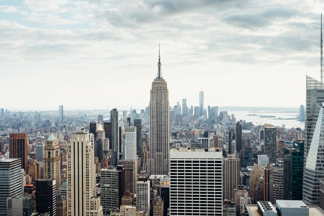 Cityscape of modern megapolis with view on skyscrapers located in New York city in America under cloudy sky in daytime