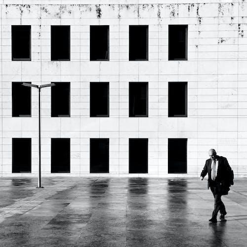 Grayscale Photo of Man Walking on Hallway