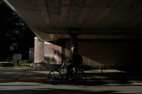 Man in Black Jacket Riding Bicycle on Road