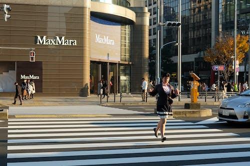 Man in Black Jacket and Black Pants Walking on Pedestrian Lane