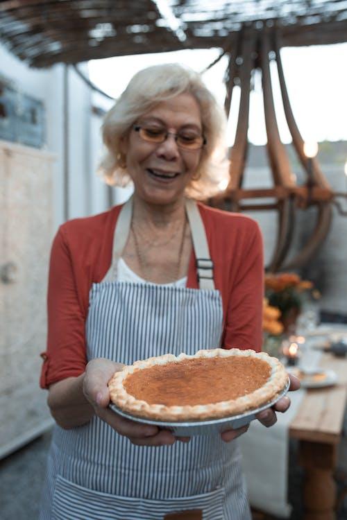 Smiling Elderly Woman Carrying a Pumpkin Pie