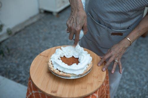 갈색 나무 라운드 테이블에 흰색 라운드 케이크를 들고 사람