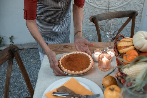 Person Placing a Pumpkin Pie on Wooden Table