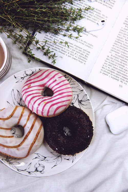 Top view of delicious glazed donuts on plate with bunch of twigs placed on opened book and earbuds in case