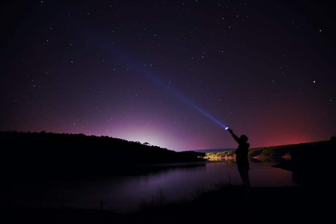 Man Standing on Lake Shore during Night Time