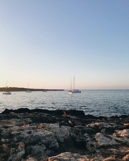 Rippling sea with boats near rocky coast