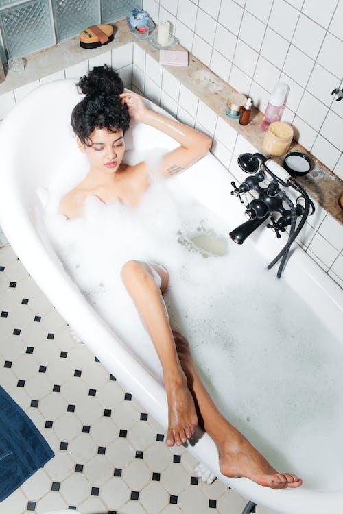 Naked Woman in White Bathtub