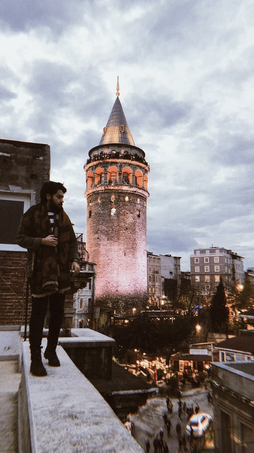 Full length contemplative bearded ethic male in warm clothes standing on snowy rooftop against medieval stone Galata Tower in Istanbul on cloudy winter day