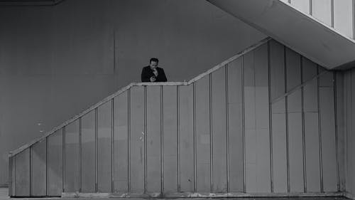 Black and white emotionless adult male in black jacket smoking cigarette and standing on outdoor building stairway