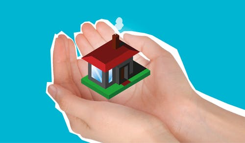 Cutout paper composition with house in handful showing concept of buying private apartment against blue background