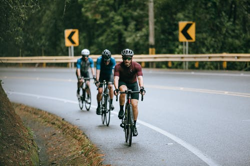 Anonymous male cyclists in sportswear and helmets riding bicycles on fenced asphalt roadway in summer