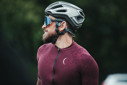 Smiling sportsman in helmet and cycling glasses on street