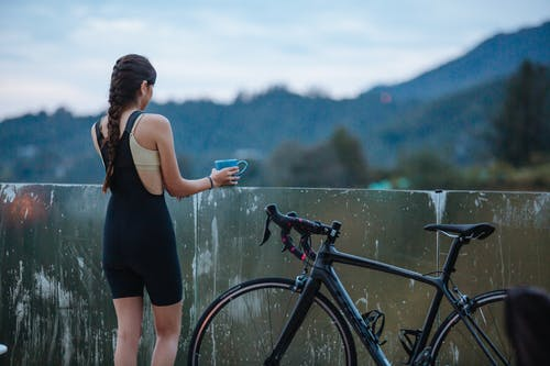 Unrecognizable sportswoman with cup near bike and fence