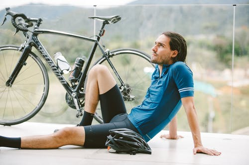 Side view of young contemplative fit male athlete in sportswear sitting near bicycle on fenced terrace while looking up