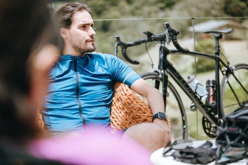 Contemplative male athlete near bicycle and anonymous friend