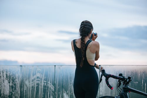 Back view of unrecognizable sportswoman drinking beverage from mug near bicycle and fence while having break