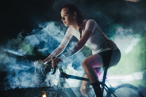 Young female athlete in active wear with concentrated gaze riding bicycle in shiny cloud while looking forward