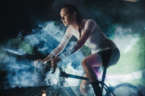 Focused sportswoman riding bike in artificial smoke