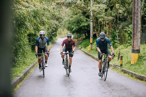 Unrecognizable male athletes in active wear and helmets riding bikes on asphalt roadway between lush green trees