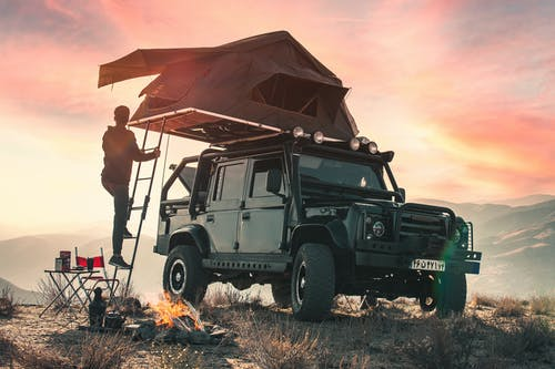 Back view of crop anonymous male traveler watching sunset during camping in mountains and climbing upstairs to tent located on roof of contemporary offroader