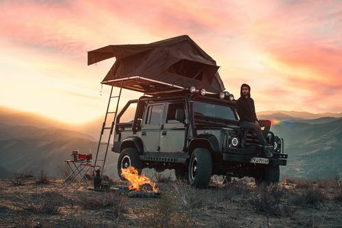 Black Jeep Wrangler With Brown Wooden Tent on Top