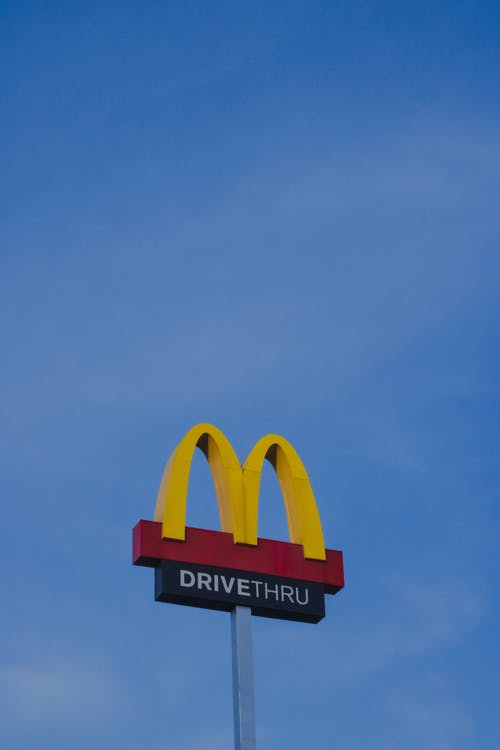 From below of colorful logo signage of modern fast food restaurant with inscription against blue cloudless sky