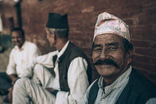 Smiling ethnic man with friends near brick wall