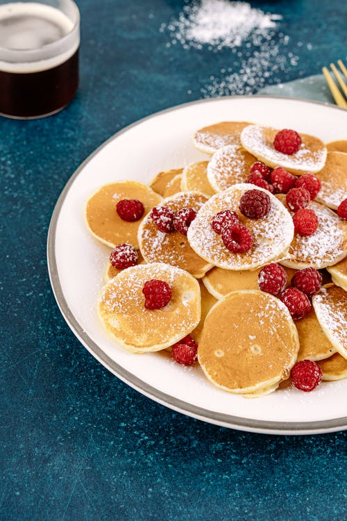 A Plate of Mini Pancakes with Raspberries