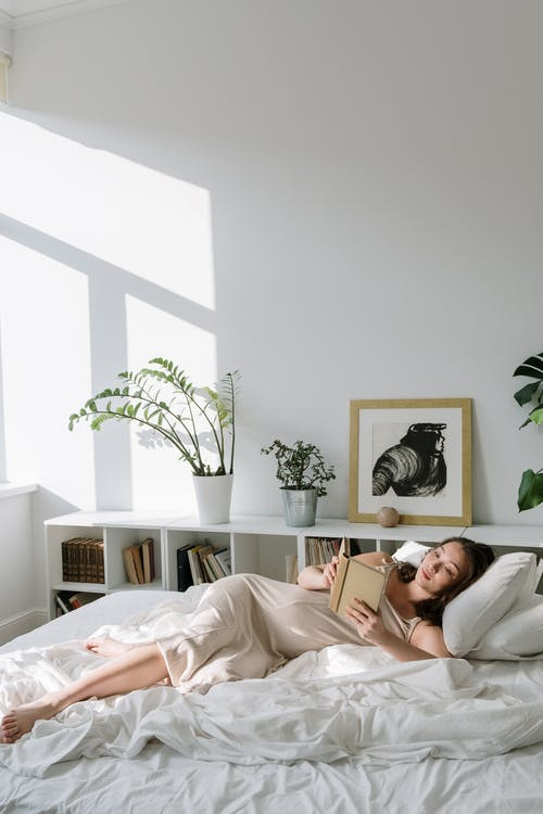Woman Lying on Bed Reading Book