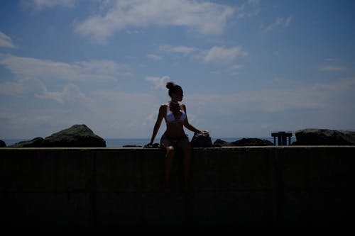 Woman in Black Bikini Sitting on Concrete Wall