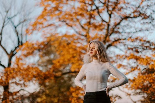 Woman in White Knit Sweater Standing Under Brown Tree