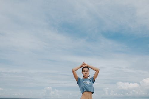 Woman in Blue Tank Top and Blue Denim Shorts Raising Her Hands Under White Clouds and
