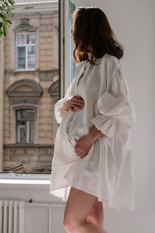 Женщина в белом платье с длинным рукавом стоит перед белым бетонным зданием
