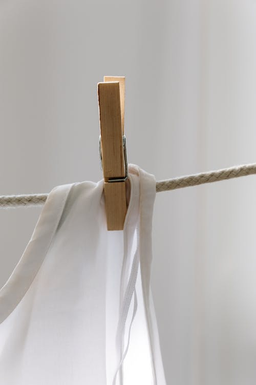 White Textile on Brown Wooden Clothes Hanger