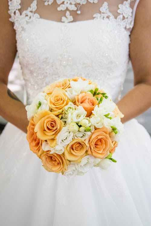 Person in White Bridal Gown Holding Flower Bouquet