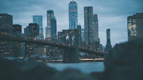 City Skyline Across Bridge during Night Time