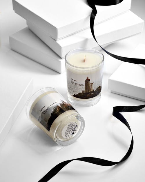 From above of glass jars of scented candles with stickers filled with white wax on table with black ribbon and white boxes