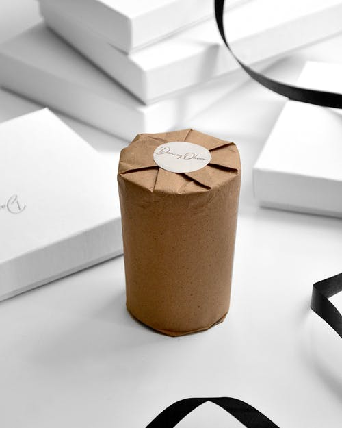 Scented candle wrapped in craft paper placed on table with heap of white boxes and black ribbon in modern studio