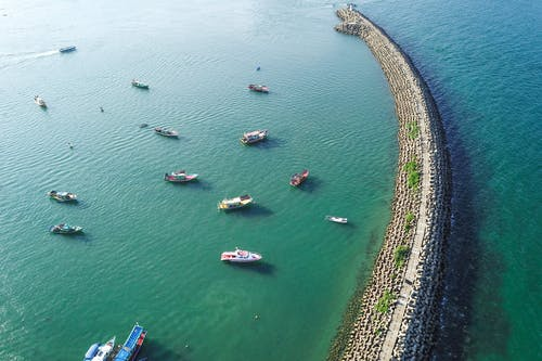 Aerial view of turquoise tranquil sea with massive long breakwater construction and many motorboats on clear weather