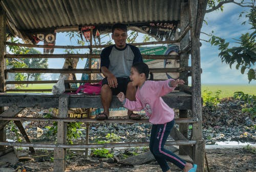Side view of cheerful little Asian girl in casual clothed smiling and running while spending time with happy father sitting in rustic wooden cabin in village