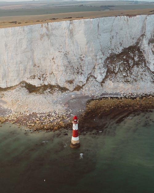 Lighthouse in sea near cliff